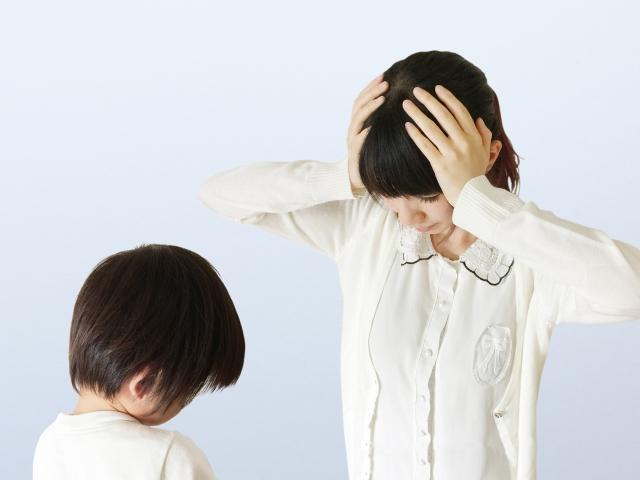 頭を抱えるママ